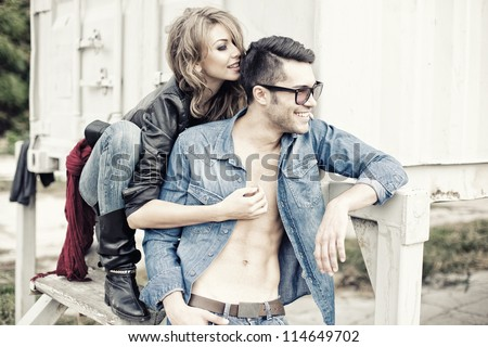 stylish couple wearing jeans and boots smiling - retro processed image - stock photo