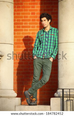 stylish curly guy in the sunshine leaning against column - stock photo