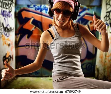 Stylish dancing girl against graffiti background - stock photo