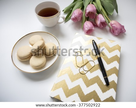 stylish desktop with notebook, tea and cookies