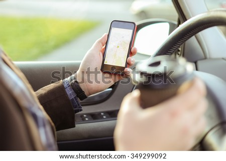 Stylish driver with a smart phone in hand and paper cup of hot coffee in the driver's seat. The concept of inattention at the wheel, rest, coffee break to cheer. - stock photo