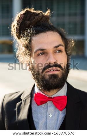 Stylish elegant dreadlocks businessman in business landscape - stock photo