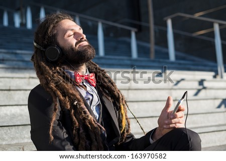 Stylish elegant dreadlocks businessman listening music in business landscape - stock photo