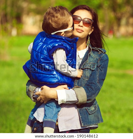 Stylish family concept. Portrait of fashionable baby boy and his gorgeous mother in trendy eyewear walking in the street. Mom hugging son. Child kissing mommy. Sunny spring day. Outdoor shot