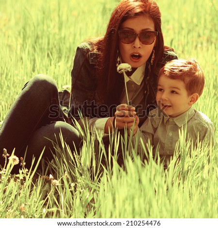 Stylish family concept. Portrait of fashionable baby boy and his gorgeous mother in trendy eyewear playing with dandelion in the park. Sunny spring day. Close-up. Outdoor shot - stock photo