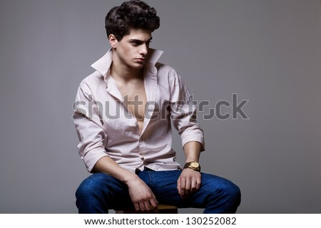 stylish fashion man model sitting on the chair with watch on his hand - stock photo