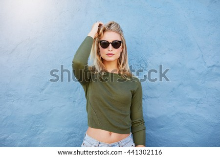 Stylish fashion portrait of trendy casual young woman. Beautiful young female model in casual clothes and sunglasses posing on blue wall - stock photo