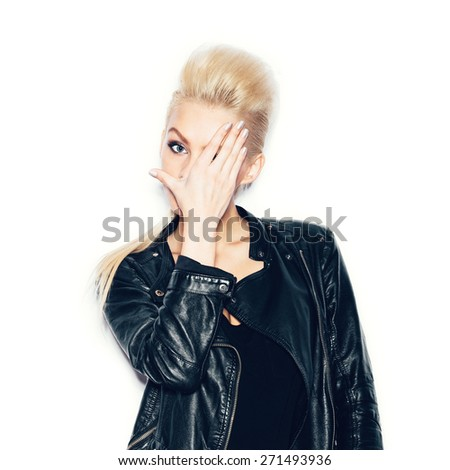Stylish fashionable blonde woman in black clothes covered her face with her hand. White background, not isolated - stock photo