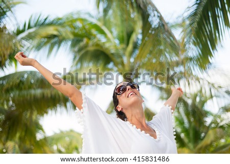Stylish fashionable woman having fun and enjoying relaxing summer tropical vacation at beach. Female brunette wearing fashion white kaftan and sunglasses raising arms. - stock photo