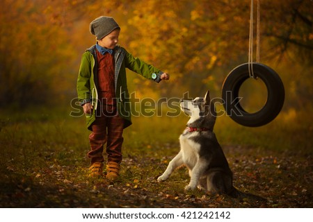 Stylish fashionable young boy playing with husky puppy dog in the woods. Near wheel swing. Autumn, the sun shines brightly. Modern man, he has family. Fashion style, vintage - stock photo