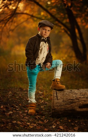 Stylish fashionable young boy stands in a fallen tree in the forest. Autumn, the sun shines brightly. Modern man, he has family. Fashion style. Dressed in 30s style, vintage - stock photo