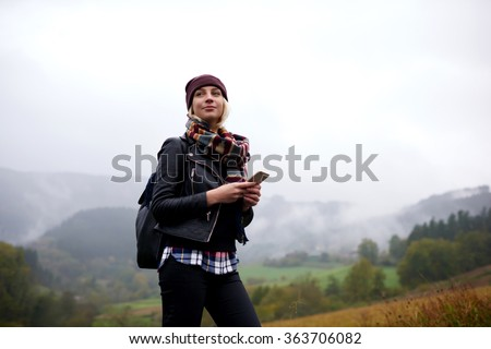 Stylish female tourist holding cell telephone while enjoy the beautiful landscape of mountains,trendy woman traveler orienteering on compass with mobile phone apps while hiking with backpack in forest - stock photo