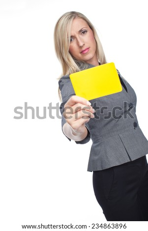 Stylish frowning woman holding up a yellow card to the camera showing that a flagrant foul has been committed, isolated on white - stock photo