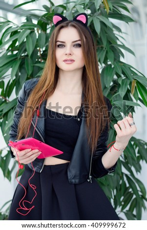 Stylish girl model wearing cat ears holding pink tablet and listen music. Indoor young female portrait wearing leather jacket and black skirt. Fashion lady with long brown hair wear cool outfit - stock photo