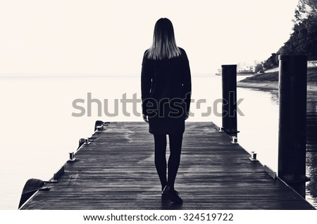 Stylish girl on a seaside pier. Black and white photography, soft focus - stock photo