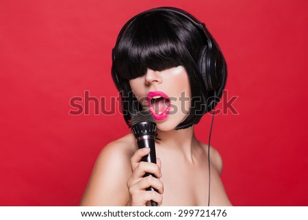 Stylish girl singing with a mike, red background - stock photo