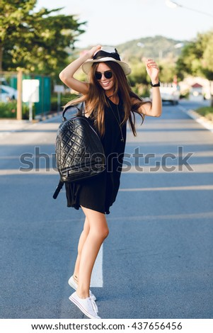 Stylish girl standing near road wearing short black dress, straw hat, black eyeglasses, white sneakers and black backpack. She smiles and dances in the warm rays of setting sun.