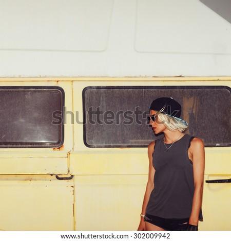 Stylish Girl stands near Minibus. Surf Fashion style - stock photo