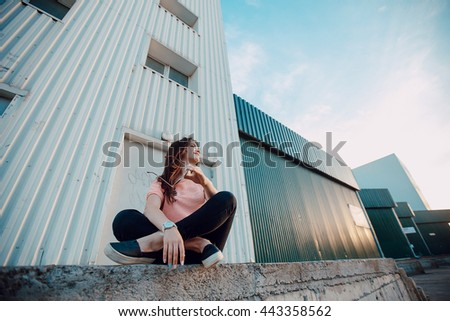 stylish girl walking in the evening city with a phone and a headset - stock photo