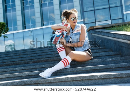 Stylish girl with a skateboard sitting on the stairs in city center