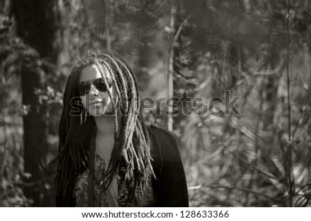 Stylish girl with dreadlocks in the trees