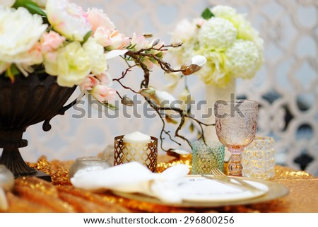 Stylish gold table set with natural flowers  - stock photo