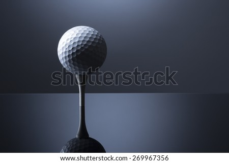Stylish golf ball on tee isolated on dark blue background with reflection, copy space for text. - stock photo