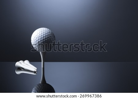 Stylish golf ball on tee with tees lying aside, isolated on dark blue background with reflection, empty copy space for text.