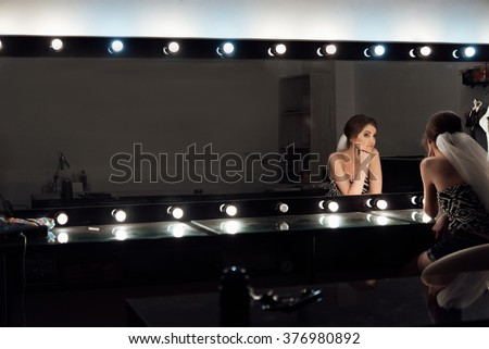 stylish gorgeous bride getting makeup in the luxury beauty saloon with big mirrors and light - stock photo