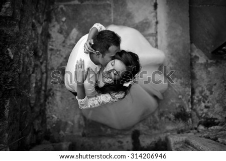 stylish gorgeous hairy brunette bride and elegant groom on the background of an old road near a castle, a top-bottom view - stock photo