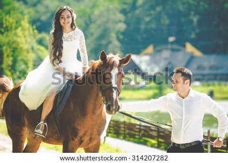 stylish gorgeous happy brunette bride on the horse and elegant groom on the background of a park