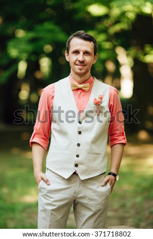 Stylish groom portrait with bow-tie in waistcoat on a park at a wedding day