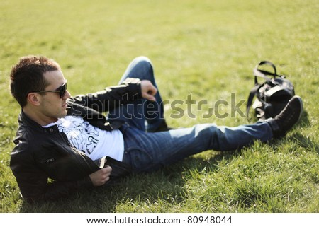 stylish guy relaxing on lawn in park