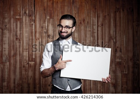 Stylish guy with a white sign for text on wooden background, ready for your text or product - stock photo
