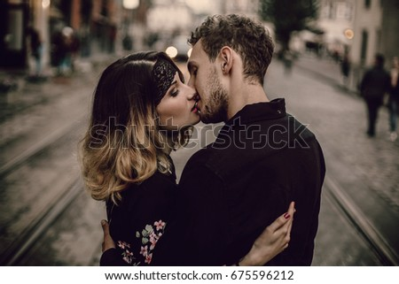 stylish gypsy couple in love kissing hugging in evening city street. woman and man gently embracing, romantic french atmospheric moment. love mood. gypsy wedding