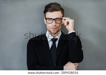 Stylish handsome. Confident young businessman adjusting his eyewear and looking at camera while standing against grey background - stock photo