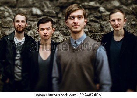 stylish handsome group of confident and successful men standing  on the background of city street - stock photo