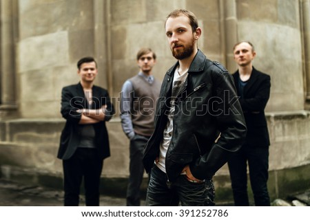 stylish handsome group of men standing and posing on the background of city street - stock photo