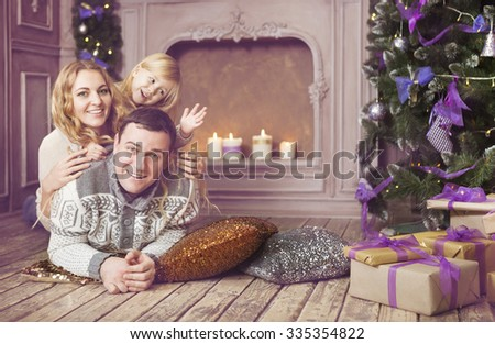 Stylish happy family celebrating christmas in room near the christmas tree