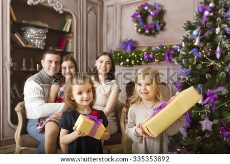 Stylish happy family celebrating christmas in room over christmas tree - stock photo