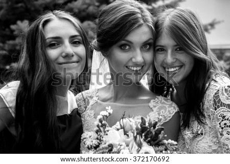 stylish happy guests and bride and bridesmaids having group photos on the sunny wedding day - stock photo