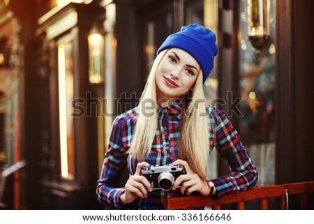Stylish happy smiling hipster girl with retro vintage camera. Close up street portrait. Model looking at camera. Toned - stock photo