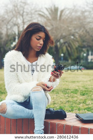 Stylish hipster girl holding smart phone while sitting in the park outdoors, attractive afro american woman using cell phone while chatting or reading text message, young teenager holding mobile phone - stock photo
