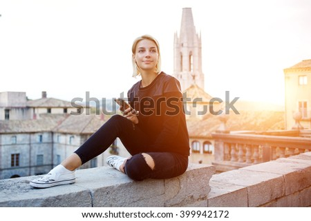Stylish hipster girl looking away, while is awaiting answer in text message on mobile phone from her friend. Young attractive student is using cell telephone during rest between lectures in University - stock photo