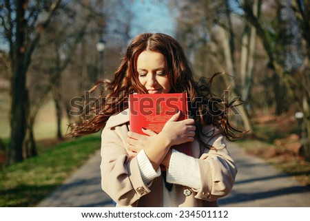 Stylish hipster smiling girl student with the book in the park outdoor