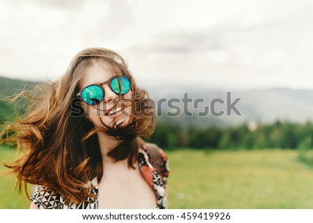 stylish hipster woman traveler with fashionable sunglasses and windy hair with confident look posing on top of mountains in summer, travel concept, space for text