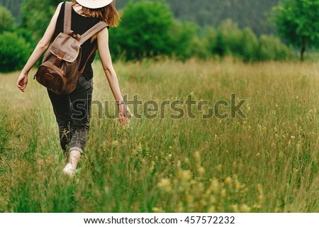 stylish hipster woman walking in grass and holding  in hand herb  wildflowers  in summer mountains, travel concept, peaceful relaxing moment - stock photo
