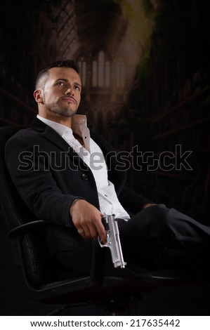 Stylish hispanic young handsome man model mobster spy hitman killer looking up sitting in a chair holding a gun over dark background - stock photo