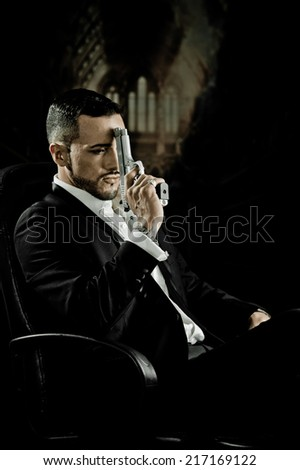 Stylish hispanic young handsome man model mobster spy hitman killer sitting in a chair holding a gun against his forehead - stock photo