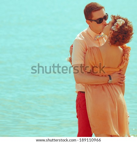 Stylish honeymoon concept. Young happy married couple of hipsters in trendy clothes, eyewear and accessories standing and kissing on the beach. Sunny summer day. Copy-space. Outdoor shot